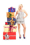 Woman standing next to a stack of presents Royalty Free Stock Photography
