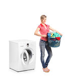 Woman standing next to a washing machine Stock Images