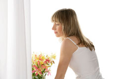 Woman standing next to window Stock Photo