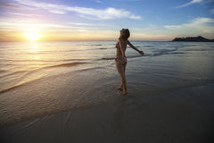 Woman standing on an ocean beach to meet the amazing sunset. Stock Photography