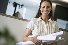 Woman standing in office, carrying rolls of blueprints, smiling, portrait (tilt, differential focus) Royalty Free Stock Images