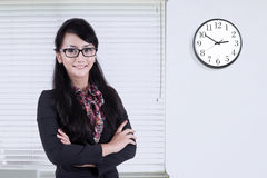 Woman standing in office with clock on the wall Stock Photography