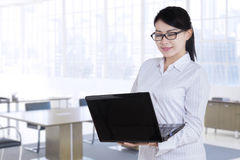 Woman standing in office and use laptop Stock Image