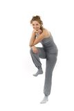 Woman standing on one leg. Woman in workout clothes or sweats, standing on one leg.  White background Stock Photo