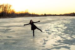 Woman Standing on One Leg on the Ice on the Frozen Platte River in Winter at Sunset stock image