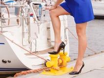 Woman standing one leg on marina bitt Stock Images