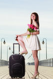 Woman standing one leg on suitcase, summertime Royalty Free Stock Photo