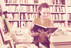 Woman standing with open in publishers store Stock Images