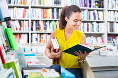 Woman standing with open in publishers store Royalty Free Stock Image