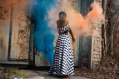 Woman Standing on Orange and Blue Smoke Stock Photography