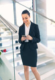 Woman standing out of office emails on phone. Woman standing out of office emails on mobile phone royalty free stock photo