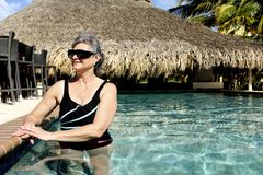 Woman standing in an outdoor Pool. In a Caribbean Resort stock photography
