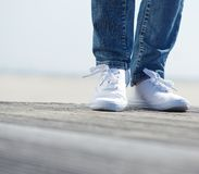 Woman standing outdoors in blue jeans and comfortable white shoes Royalty Free Stock Photo