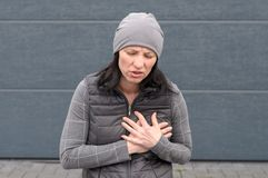 Woman in a grey winter outfit clutching her chest. Woman standing outdoors in a grey winter outfit clutching her chest with both hands and grimacing in pain in a royalty free stock images