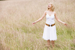 Woman standing outdoors holding grass smiling Royalty Free Stock Image