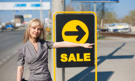 Woman standing outdoors near a banner Stock Images