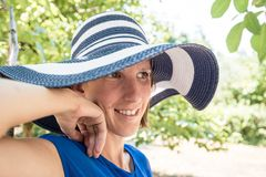Woman standing outdoors in a stylish sunhat. Woman standing outdoors in a stylish wide brimmed blue and white sunhat in the shade of a garden tree with a smile Royalty Free Stock Photography