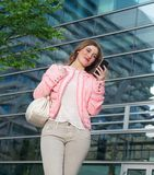 Woman standing outside building and sending text message on cellphone Royalty Free Stock Photo