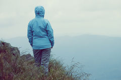 Woman standing over cliff. In mountains Stock Photography