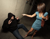 Woman standing over the robber. Who she just assaulted while the man is on the ground asking for mercy royalty free stock image
