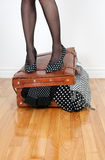 Woman standing on overfilled suitcase. Woman in high heel shoes standing on leather suitcase overfilled with fashion clothing Royalty Free Stock Photography