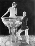 Woman standing in an oversized glass with a man trying to lift it Royalty Free Stock Images