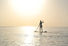 Woman Standing on Paddleboard on Body of Water Royalty Free Stock Image