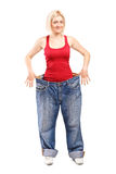 Woman standing in a pair of oversized jeans Stock Photos