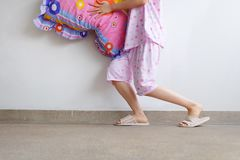 Woman Standing with A Pair of Warm Pink Shoes. Female Legs in Pink Pajama Pants and Checkered Slippers on The Floor Background. Great For Any Use Royalty Free Stock Photo