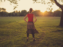 Woman standing in park admiring the sunset Royalty Free Stock Photo