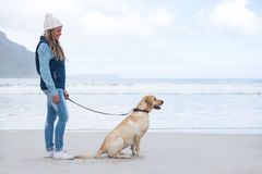 Woman standing with pet dog. At the beach Stock Photo