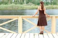 Woman standing at pier. Woman standing at the pier's railing, looking at the water Stock Image