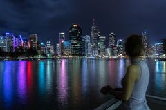 Woman standing on pier in Brisbane. Female at observation point looking on illuminated town with tall highlighted skyscraper and coast with foliage and colorful royalty free stock photo