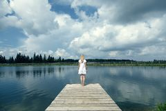 Woman standing on pier at the lake stock photography