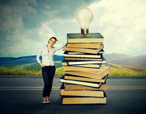 Woman standing by pile of old books with bright light bulb on top of it Royalty Free Stock Image
