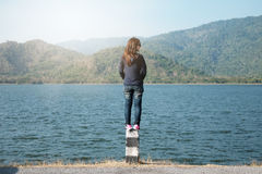 Woman standing on pillar roadside front of her have big lake and Stock Image
