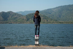 Woman standing on pillar roadside front of her have big lake and Stock Photos