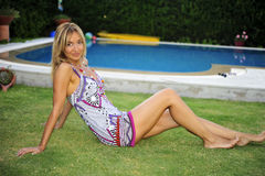 Woman standing by pool. A young attractive woman standing by pool royalty free stock photos