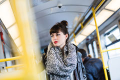 Woman standing in public transportation. Young woman standing in public transportation transit in train or tramway. Color toned image. Selective focus Royalty Free Stock Photo