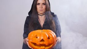 Woman is standing with the pumpkin in smoke stock video footage