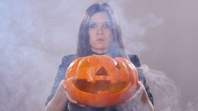 Woman is standing with the pumpkin in smoke stock video