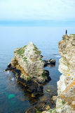 Woman standing with raised hands against the edge of  cliff on  black sea , . Royalty Free Stock Images