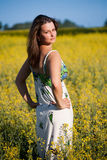 Woman standing in rape field Royalty Free Stock Image