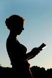 Woman standing and reading book, trees, side view Royalty Free Stock Image