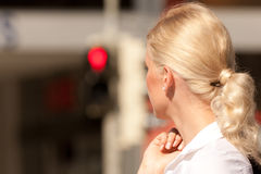 Woman standing at red traffic light stock images