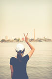 The woman standing on river side and show two finger while looki Royalty Free Stock Photography