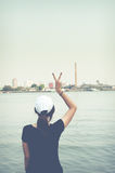 The woman standing on river side and show two finger while looking scenery Royalty Free Stock Photo