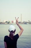 The woman standing on river side and show two finger while looking scenery Royalty Free Stock Images