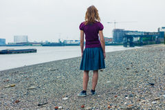 Woman standing on riverbank Stock Images