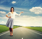 Woman standing on the road. Attractive young woman standing on the road and pointing at something Royalty Free Stock Photos